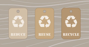 Reduce reuse recycle tags. Over a wood table Royalty Free Stock Photo
