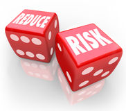 Reduce Risk Words Red Dice Lower Liability Chance Bet Gamble. Reduce Risk words on two red dice to illustrate lowering your chances for liability, danger, hazard Stock Image