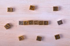 Reduce word metal block. Reduce word gold and silver metal block on white wood with letter blocks around royalty free stock image