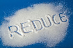 REDUCE written with sugar. Sugar on a blue background with warning message REDUCE written on it. Health concept. Diabetes hazard Stock Image
