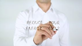 Reduce Your Energy Bill, Man Writing on Glass. High quality stock images