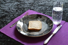 Reduced meal in Lent with bread and water. Reduced meal in Lent with a slice of bread on a plate and a glass of water stock photos