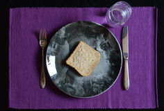 Reduced meal in Lent with bread and water. Reduced meal in Lent with a slice of bread on a plate and a glass of water royalty free stock image