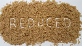 Reduced Spelled Out in Brown Sugar. Reduced Sugar. Reduced Spelled Out in Brown Sugar on White Background. Reduced Sugar royalty free stock photography