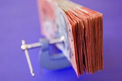 Reduced spending. A wad of australian 20 dollar notes pressed in a G clamp Royalty Free Stock Photo