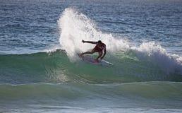 Reduciendo radicalmente a la persona que practica surf - playa de hombres Imagen de archivo libre de regalías