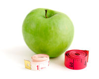 Reducing aids. Green apple, and two tailors meter isolation on a white background Royalty Free Stock Photos
