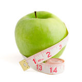Reducing aids. Green apple measured dressmaker meter isolated on a white background Stock Image