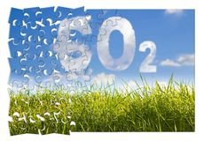 Reduction of CO2 presence in the atmosphere - jigsaw puzzle concept image against a green wild grass on sky background.  stock image