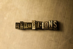 REDUCTIONS - close-up of grungy vintage typeset word on metal backdrop. Royalty free stock illustration. Can be used for online banner ads and direct mail royalty free illustration