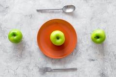 Reduktionsdiät Apple an der Platte auf Draufsicht des grauen Steinhintergrundes Stockbild