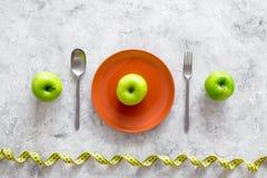 Reduktionsdiät Apple an der Platte und an messendem Band auf Draufsicht des grauen Steinhintergrundes Lizenzfreies Stockfoto