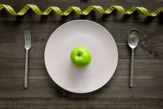 Reduktionsdiät Apple an der Platte und an messendem Band auf Draufsicht des hölzernen Hintergrundes Lizenzfreies Stockfoto