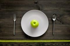 Reduktionsdiät Apple an der Platte und an messendem Band auf Draufsicht des hölzernen Hintergrundes Stockfoto