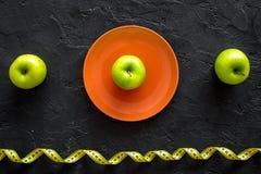 Reduktionsdiät Apple an der Platte und an messendem Band auf Draufsicht des schwarzen Hintergrundes Stockbilder