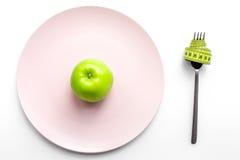 Reduktionsdiät Apple an der Platte und an messendem Band auf Draufsicht des weißen Hintergrundes Lizenzfreie Stockfotografie