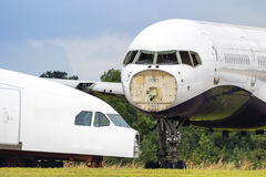 Redundant Passenger Airliners Being Dismantled. Close up of two redundant passenger airliners being dismantled in a field Royalty Free Stock Photo