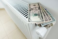 Reduza sua conta de energia para o aquecimento da casa com cédulas dos dólares americanos no radiador branco fotos de stock royalty free