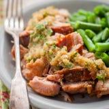 Reduzca el cerdo cocinado con la compota de manzanas y las habas verdes Imágenes de archivo libres de regalías