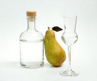 Reduzca la pera de Fetel con la botella y el vidrio del alcohol Imagenes de archivo