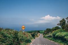 Reduzca la señal de peligro abajo de un campo rural escarpado en el condado Kerry Foto de archivo libre de regalías