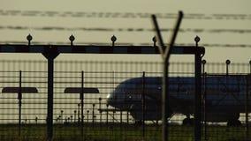 Redy vliegtuig om in silhouet tegen een oranje zonsonderganghemel op te stijgen stock video