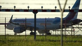 Redy vliegtuig om in silhouet tegen een oranje zonsonderganghemel op te stijgen stock footage