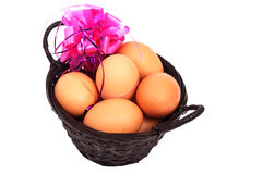 Reed basket with Easter eggs and pink decoration ribbon Royalty Free Stock Images