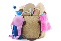 Reed beach bag filled with bikini, slippers, water etc Royalty Free Stock Image