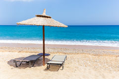 Reed beach umbrella with loungers on beach at sea Royalty Free Stock Photo