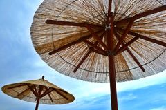 Reed beach umbrellas with the blue sky and clouds. royalty free stock images