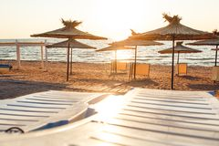 Reed beach umbrellas and sunbeds on sandy seashore in sun. stock photos