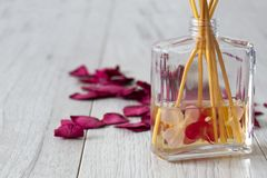 Reed diffuser with fragrance in a glass jar with rose petals. On a grey wood background stock image