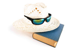 Reed hat, sunglasses and book. Holiday theme Royalty Free Stock Image