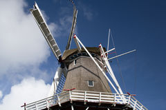 Reed hood or classical windmill against blue sky with clouds. You can see the whire wooden construction with red tips Stock Photos