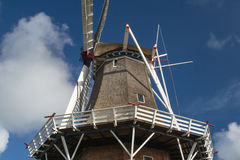 Reed hood or classical windmill against blue sky with clouds. You can see the white wooden handrail and other wooden parts with red tips Stock Photography