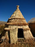 Reed hut at Lake Titicaca. The pre-Incan Aymara people of the Uros Islands on Lake Titicaca in Peru have a heavy reliance on reeds for their existence Stock Photos