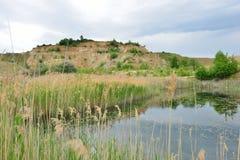 Reed and kaolin hill at the Blue Lagoon lake. Stock Photography
