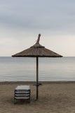 Reed Parasol With Sun Loungers auf Sandy Beach Regenschirm und Sunbeds auf düsterem Wetter und ruhigem See Reed Umbrella und Sess Lizenzfreies Stockbild