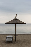 Reed Parasol With Sun Loungers on Sandy Beach. Umbrella and Sunbeds on Gloomy Weather and Calm Sea. Reed Umbrella and Easy Chairs. Royalty Free Stock Image