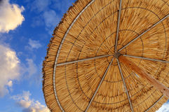 A reed sun umbrella and blue cloudy sky symbolizing vacationing Stock Photo