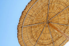 A reed sun umbrella and blue sky symbolizing vacationing in summ Royalty Free Stock Photos