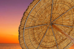 A reed sun umbrella and sun down sky symbolizing vacationing in Stock Photos