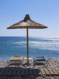 Reed umbrella and deck chairs on the sea beach Royalty Free Stock Photos