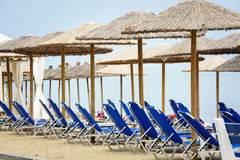 Reed umbrellas and deck chairs at the beach Royalty Free Stock Photo