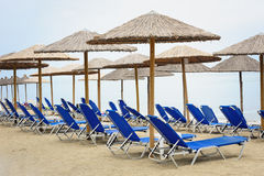 Reed umbrellas and deck chairs at the beach Stock Photography