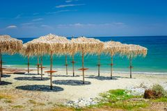 Reed umbrellas at empty beach Royalty Free Stock Photos
