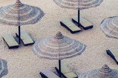 Reed umbrellas with loungers on a beautiful sandy beach.  stock image
