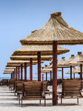 Reed umbrellas sun-beds on beach Royalty Free Stock Images