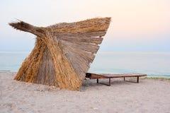 REEDregenschirm auf dem Strand im Sonnenuntergang stockfotografie